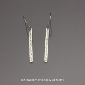 "An image of a piece of Jewellery a pair of simple stick earrings with the title ""Stick earrings with seeds/bubbles"", in sterling silver by JEK Jewellery."