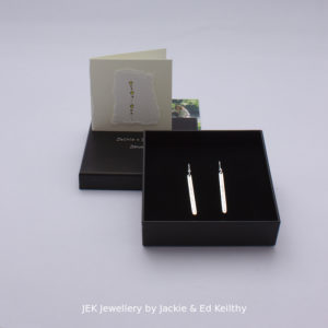 "An image of the piece title ""Stick earrings"" in its box and the hand drawn card that accompanies it and some jek business cards."
