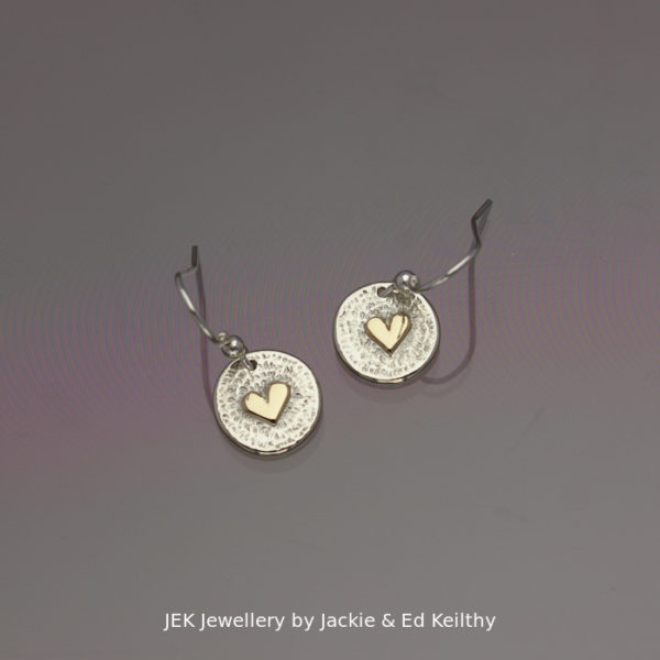 "An image of a piece of Jewellery, a pair of round earrings with the title ""Heart of Gold"" in sterling silver with 9ct Gold by JEK Jewellery."