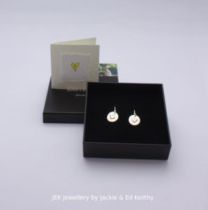 "An image of the piece title ""Heart Of Gold round earrings"" in its box and the hand drawn card that accompanies it and some jek business cards."