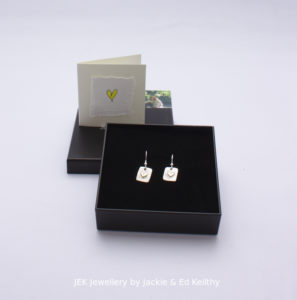 """An image of the piece title """"Heart Of Gold square earrings"""" in its box and the hand drawn card that accompanies it and some jek business cards."""