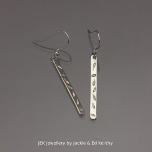 "An image of a piece of Jewellery,a pair of stick like earrings with the title "" Autumn Leaves""in sterling silver by JEK Jewellery."