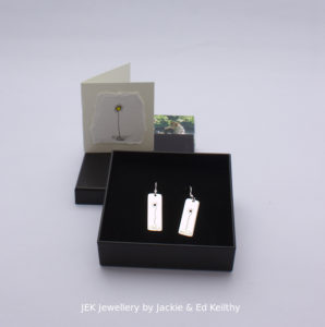 "An image of the piece title ""Sunflower earrings"" in its box and the hand drawn card that accompanies it and some jek business cards."