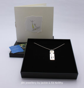 "An image of the piece title ""Mother And Child"" (boy),in its box and the hand drawn card that accompanies it and some jek business cards."