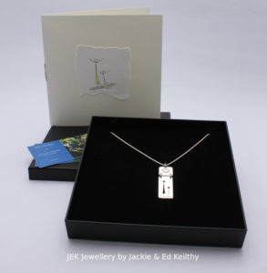 """An image of the piece title """"Mother And Child"""" (son),in its box and the hand drawn card that accompanies it and some jek business cards."""