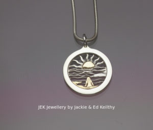 """An image of a piece of Jewellery ,a round framed pendant with the title """"Reflections"""", in sterling silver with 9ct Gold by JEK Jewellery."""