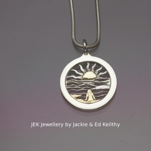 "An image of a piece of Jewellery ,a round framed pendant with the title ""Reflections"", in sterling silver with 9ct Gold by JEK Jewellery."