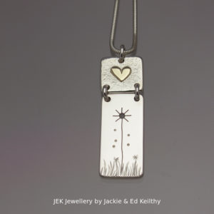 "An image of a piece of Jewellery ,a double hinged pendant with the title ""Sowing The Seeds Of Love""in sterling silver with 9ct Gold by JEK Jewellery."