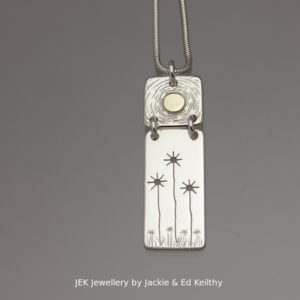 "An image of a piece of Jewellery ,a double hinged pendant with the title ""Sunflowers""in sterling silver with 9ct Gold by JEK Jewellery."