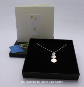 """An image of the piece title """"You Are My Sun, Moon And Stars"""" in its box and the hand drawn card that accompanies it and some jek business cards."""