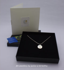 """An image of the piece title """"Reflection"""" in its box and the hand drawn card that accompanies it and some jek business cards."""