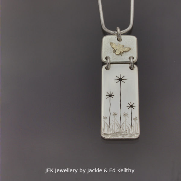 """An image of a piece of Jewellery .A double hinged pendant with the title """"Harmony"""" in sterling silver with 9ct Gold by JEK Jewellery."""